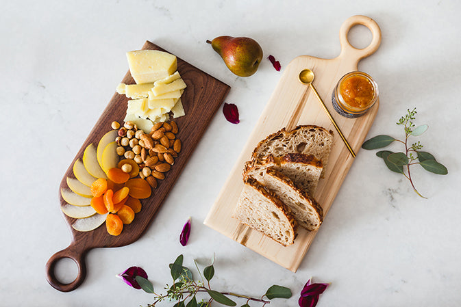 cutting boards with cheese and jam and fruit and nuts