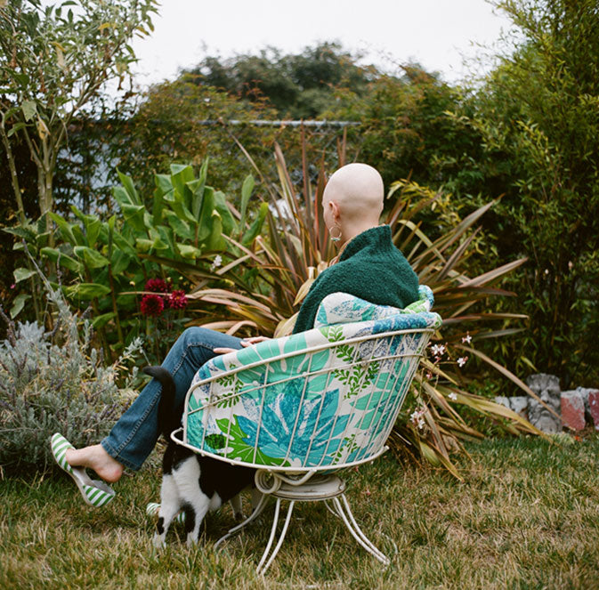 Chemo patient bald head in backyard with cat