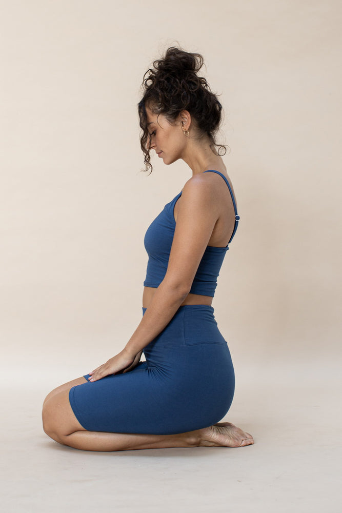 Model sitting, wearing Ananda Bike Shorts made from Certified organic Cotton, hand dyed colour French Blue