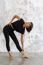 Woman doing yoga pose, wearing Ananda Capri in colour Black