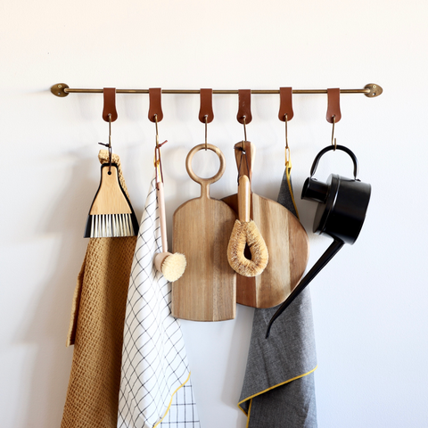 Holistic Habitat image of cleaning tools hanging on our brass rail with leather hooks