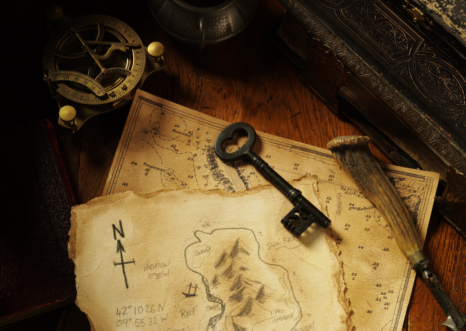 Welcome to 21 Keys Escape Rooms homepage! Image of great escape game items: key, leather book, treasure maps, ornate jewelry box, compass and dial.