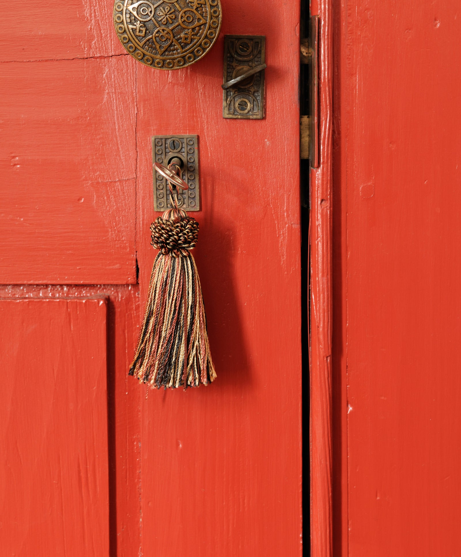 Can you escape what's behind this door?  Image of orange door with yarn tassel and antique handle.