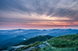 High Peaks of the Adirondacks from Algonquin Peak.  Morning clouds with pink tint hovering over tiered peaks from a lush green ADK mountaintop.