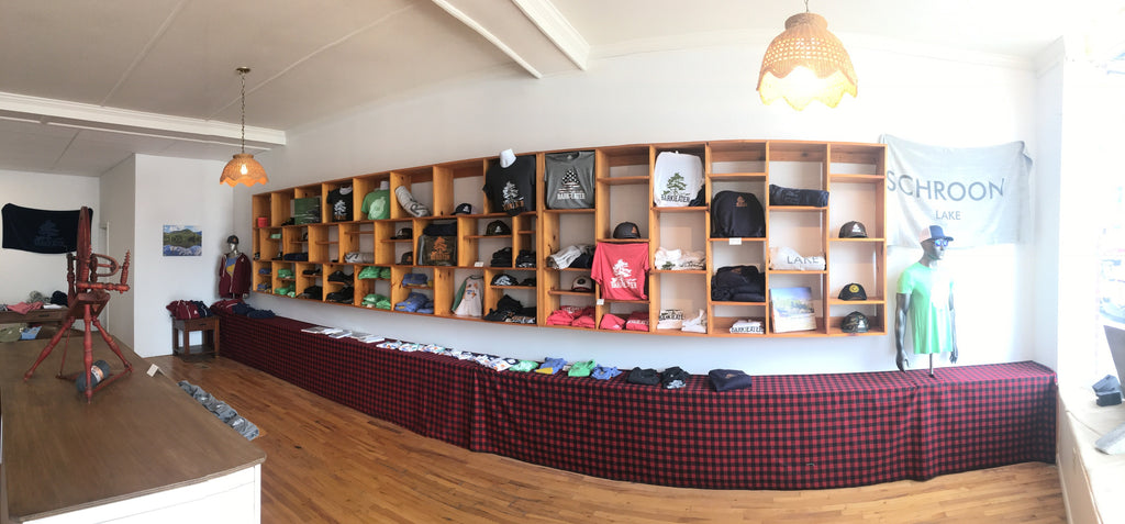 Cubbies on the wall of different shapes display Bark Eater Outfitters apparel Adirondack designs. A Buffalo red & black plaid camouflages a 2' high storage shelf. Items seen on the wall: Bark Eater unisex tee shirts, sweatshirts, mesh trucker hats