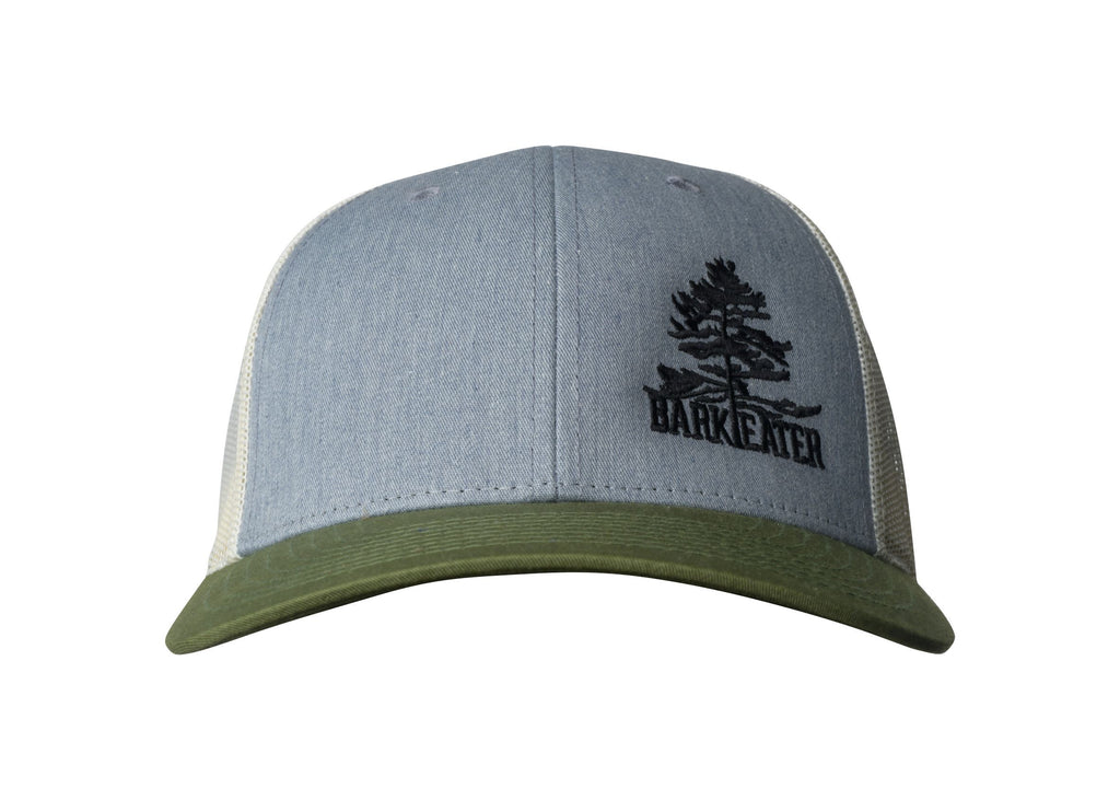 The Adirondack Trapper Trucker features the Bark Eater Outfitters logo in black off-camber on a classic grey trucker hat with amber mesh and an olive brim. Adjustable snapback.