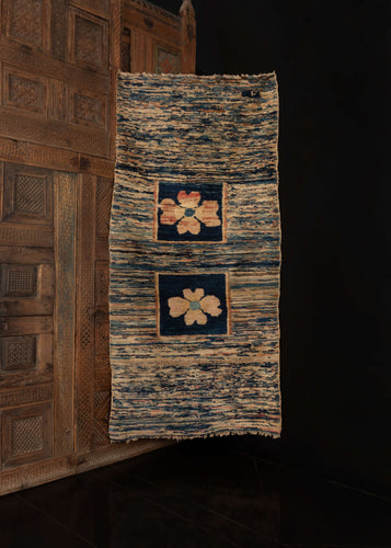 Tibetan rug handwoven in Tibet during the second quarter of the 20th century.   This rug features a minimalist design of two central flowers in deep blue squares, on a striated field of pinks, blues, and beiges, highlighting the beauty of the colors and the minimalism of the design.   In excellent condition, signs of wear consistent with age. Low pile, with a soft yet heavy handle.