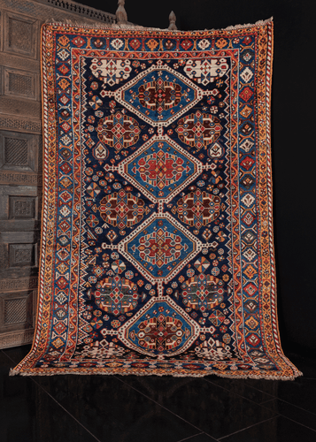 qashqa'i rug from sw iran woven during 1925-1950. medallion design on inidigo blue field filled with shapes and symbols. Color palette is composed of blues, reds, yellows, browns, whites. in excellent condition, no signs of wear.