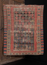 Antique Caucasian Kuba rug, handwoven during the first quarter of the 20th century. The rug is composed of a geometric design arranged diagonally, with alternating rosette and crab borders. The color palette includes bright red, deep blue, ivory, and brown, which has oxidized. In fair condition, with signs of wear throughout,