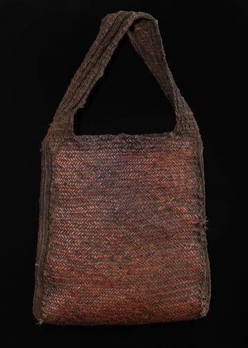 Vintage handwoven New Guinea Highlands bag.  This woven bag is braided with thin strips of rattan, giving it a stiff and sturdy form. This type of bag is called aenkiya nuw and was used by older men during ritual ceremonies and to carry accessories like tobacco pipes.   In excellent condition, signs of wear consistent with age.