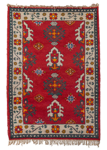Vintage Indian rug with a bright red background and funky geometric and floral design. In excellent condition, signs of wear consistent with age.