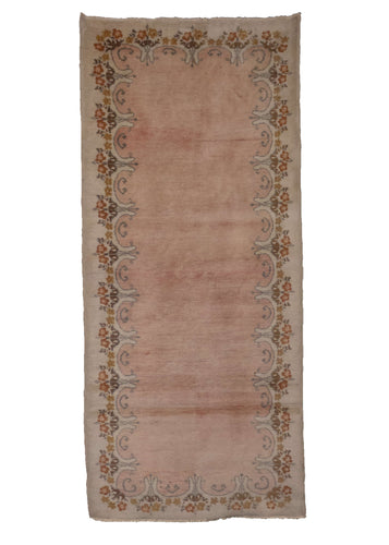 Chinese Khotan rug, handwoven during the 1980s in NW China. It features a plain soft pink field with a scalloped border. In very good condition, signs of wear consistent with age.