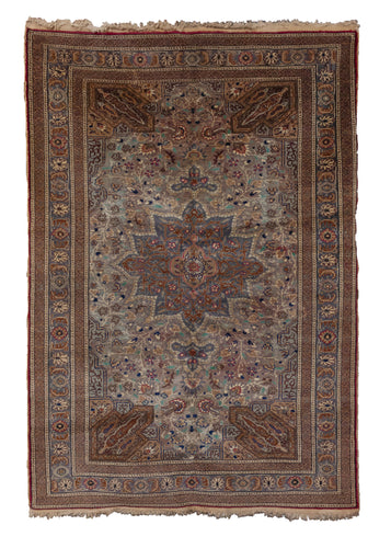Vintage Sivas rug handwoven in Turkey. It's composed of a central medallion design, with a color palette heavy on blues, greys, and browns, with pops of pink and red. In excellent condition, signs of wear consistent with age.