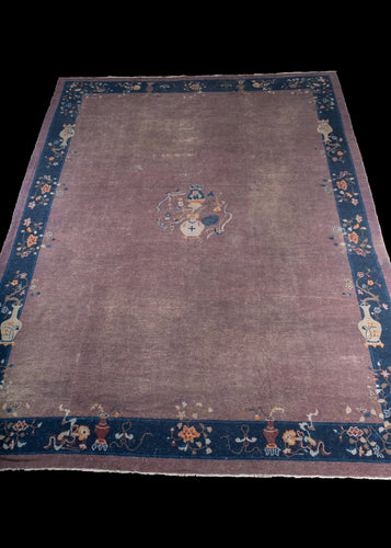 Antique Chinese lavender Peking rug with an indigo colored border. There are many flowers and vases with cream and orange accents