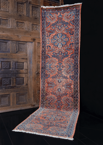 1920s Lilihan runner handwoven in Western Iran. Features delicate and ornate floral sprays in soft blues on a coral field.