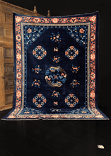 Foo-dog rug handwoven during middle of 20th century in China. Central medallion featuring two foo-dogs. Four lotus medallions and various floating floral sprays atop the deep blue indigo field.