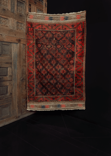 Baluch rug handwoven at border of Afghanistan and Iran during late 19th century. Honeycomb design of hexagons. Reds, blues and oxidized browns.