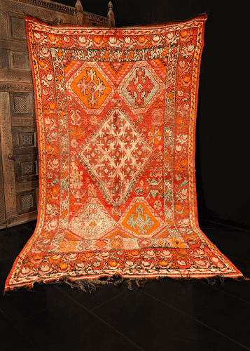 Rabat rug handwoven in Northwest Morocco during middle 20th century. Faded red field with greens, oranges, white and faded black on top. Central asymmetric latched diamond is flanked by four orange sextons and various protection symbols.