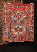 Afshar rug handwoven in South Iran during the second quarter of the 20th century. Two blossoming diamond medallions rendered in ivory, blue and brown with touches of orange and yellow on a coral field. Flowering vine composes the meandering minor border.