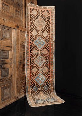 Heriz runner handwoven in Northwest Iran during the first quarter of the 20th century. Five medallions in alternating blues and browns. Red is used to highlight the details adding movement.