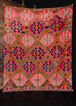 Armenian kilim handwoven during middle of the 20th century. Graphic geometric design on chocolate brown field with abrash throughout. Medallions are various shades of dark indigo to light blue. Orange details add a pop of brightness.