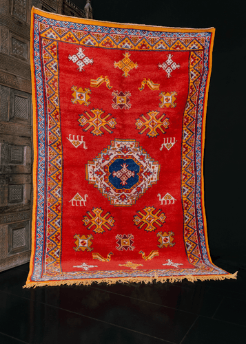 Moroccan rug handwoven during the mid 20th century. Minimal design paired with bold color palette. Bright red field contains a central medallion with smaller shapes and animals. Orange, yellow and ivory.
