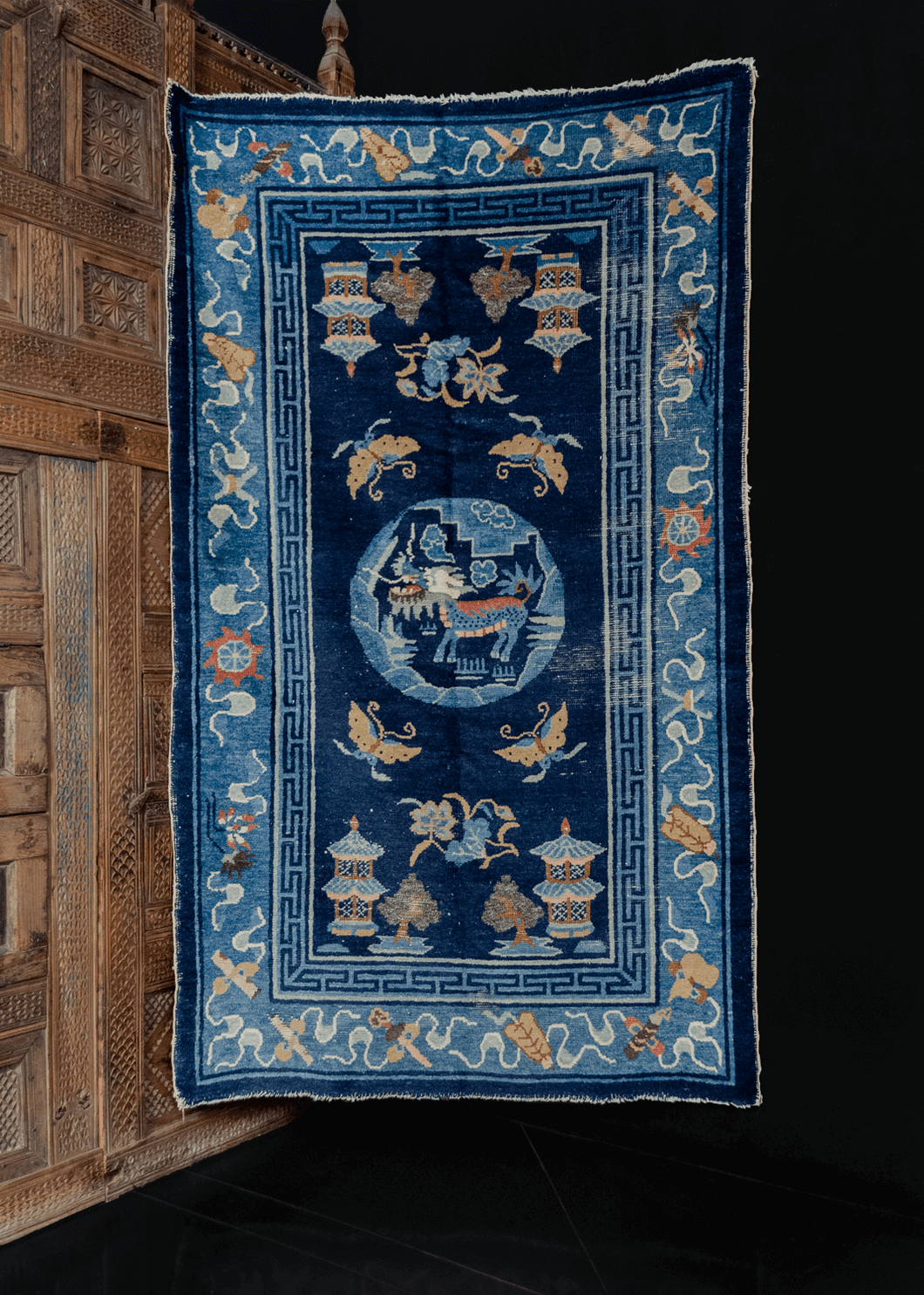 Antique Ninghxia rug handwoven early 20th century in Central China. Central medallion with dragon or foo dog surrounded by butterflies, trees and pagodas at the corners. Primarily blue with earthy yellows, reds, browns and white.