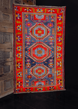 Derbent rug handwoven in the Daghestan region of Southern Russia during middle of 20th century. Bold geometric design in bright reds, purples and blues. Three central medallions with two half medallions.