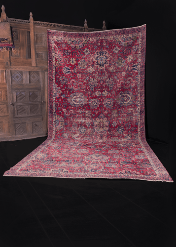 Yazd rug from C Iran featuring curvilinear floral motif on a cochineal red field with indigo blues and camels