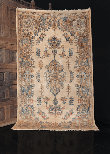 Kerman rug from C Iran with curvilinear floral motif based around central medallion on ivory field. Other colors include indigo blues and pinks. In excellent condition with very shiny wool.