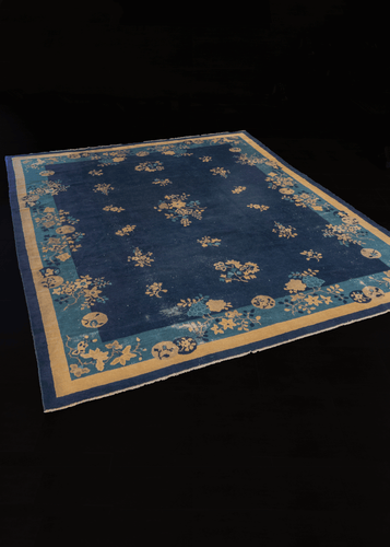 Antique indigo blue Peking rug featuring ivory blossoms.