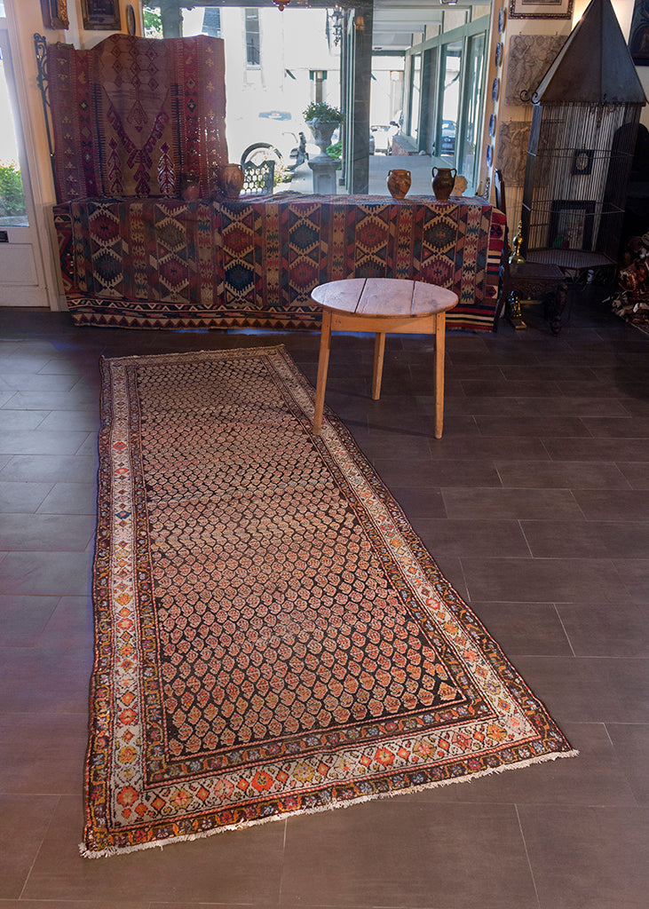 Malayer runner handwoven during second quarter of 20th century in Western Iran. Wide field with repeating multicolored boteh symbols atop dark brown field. Notes of blue, orange and yellow.