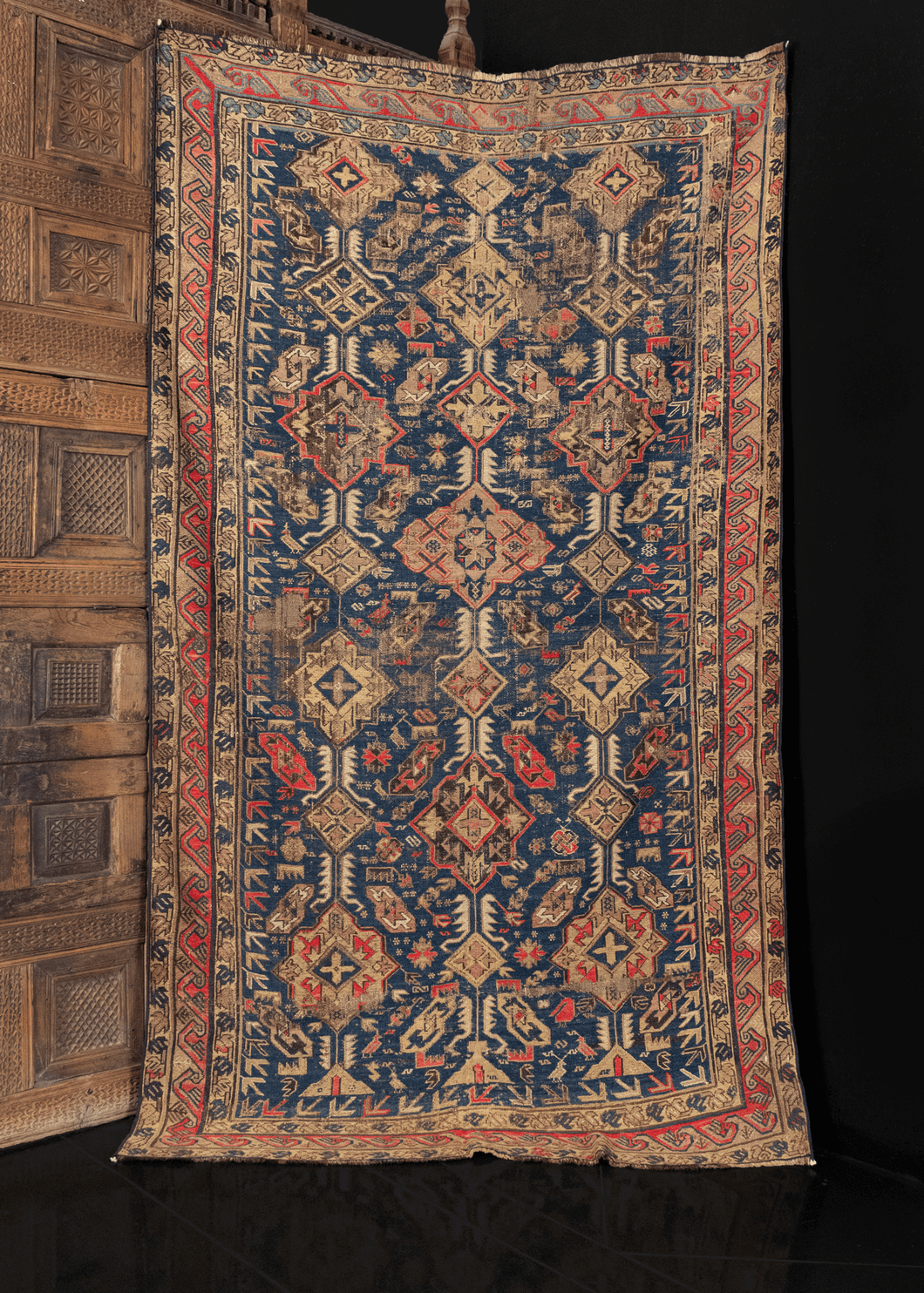 Caucasian Soumak rug with lozenge and diamond pattern on indigo blue ground. in fair condition with some wear