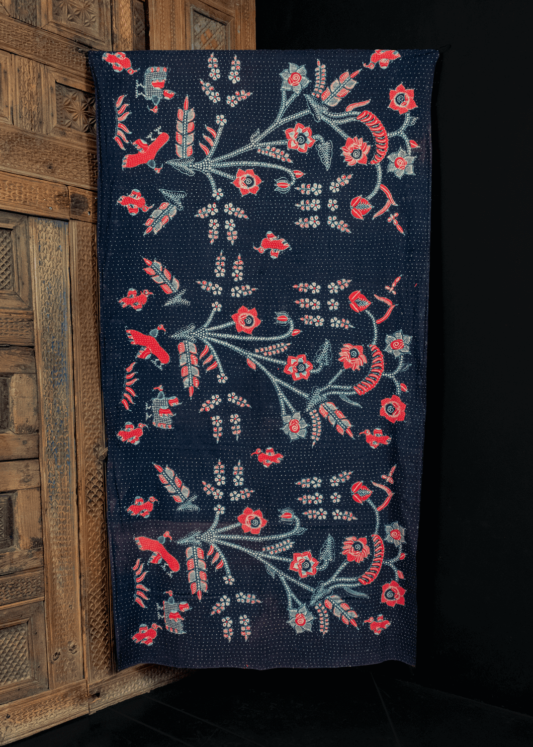 vintage skirtcloth from Java, Indonesia blockprinted with  a bouquet of flowers in red, white and blue on a dark blue ground with white polka dots. in very good condition, with some sun fading along old fold lines.