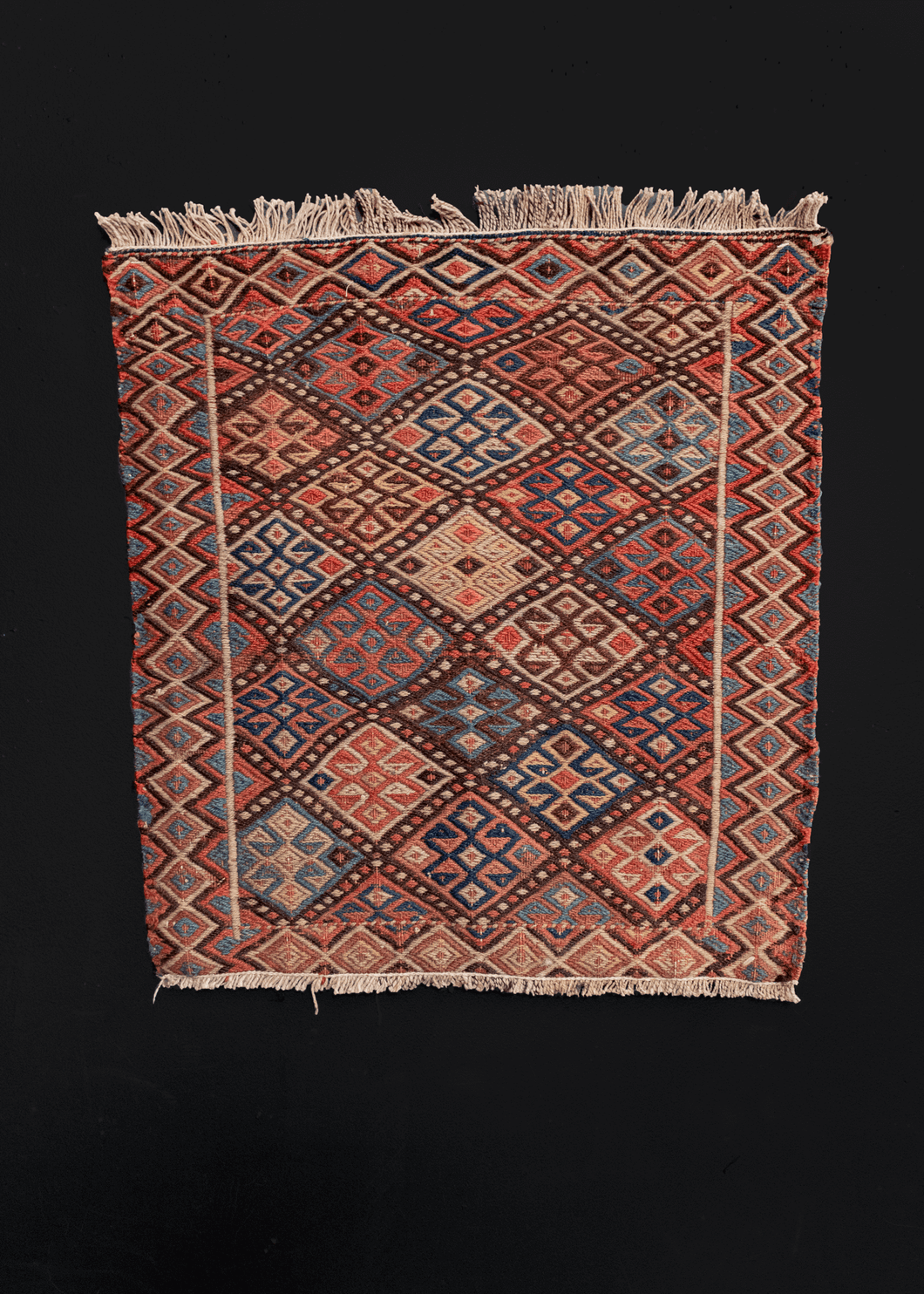 Image of small Persian Shahsavan soumak rug with colorful geometric design.