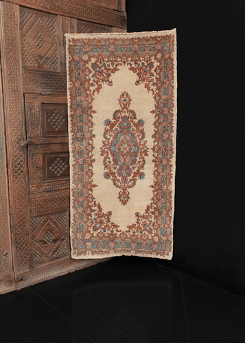 Kerman rug with ivory ground with central medallion and cornices with a curvilinear floral design. in excellent condition