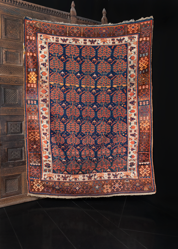 Kurdish rug handwoven during the early 20th century in Northwest Iran. Five columns of chubby paisleys on an indigo field. Ivory border encompasses and brightens the piece. Reds, blues, brown, orange and yellow.