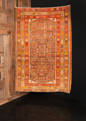 Khotan rug handwoven during the second quarter of the 20th century in Northwest China. Classic herati design framed by a serrated ivory edge with a single rosette in each cornice. Shades of orange, burnt Sienna, amber and gold.