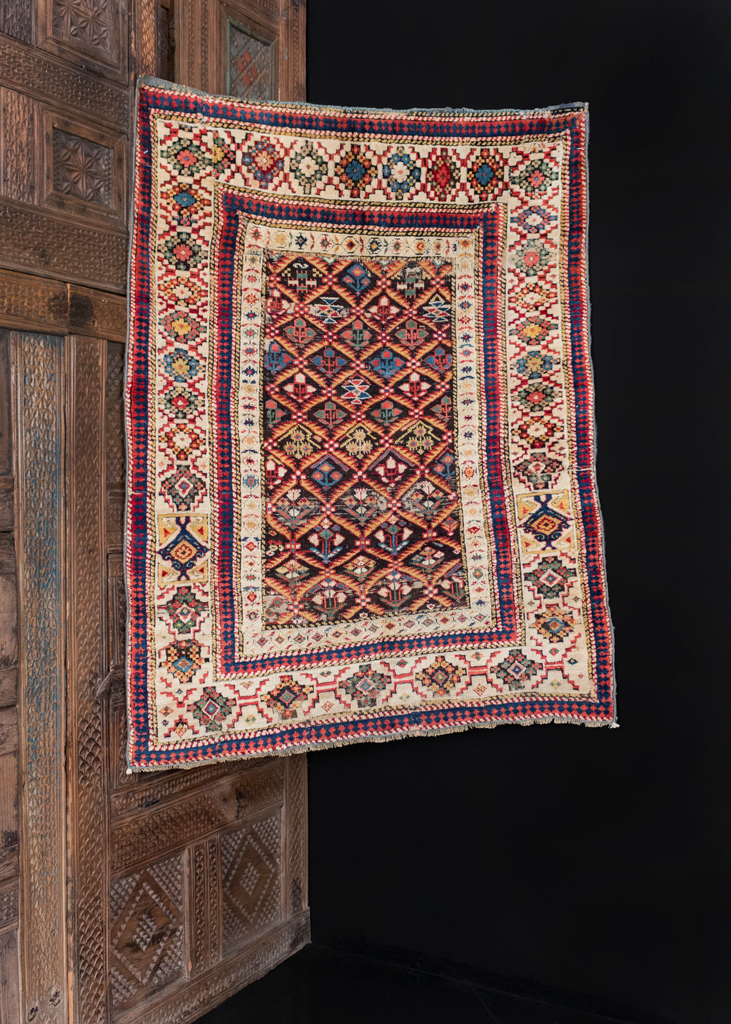 Shirvan rug handwoven during middle of 19th century in the Caucasus. Colorful array of blossoming flowers separated by yellow lattice atop dark field. Large ivory border surrounds field with brightly colored bouquets.