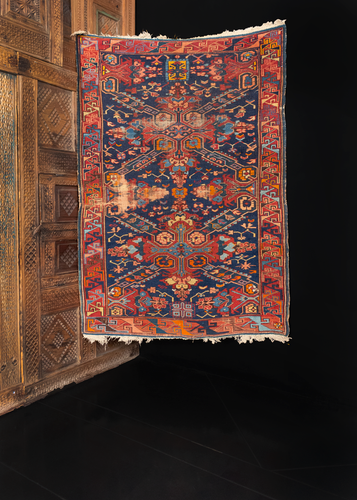 Seychur Kuba rug handwoven early 20th century in the Caucasus. Geometric cross pattern amidst a detailed floral spray. Orange, reds, and pinks atop a dark indigo ground.