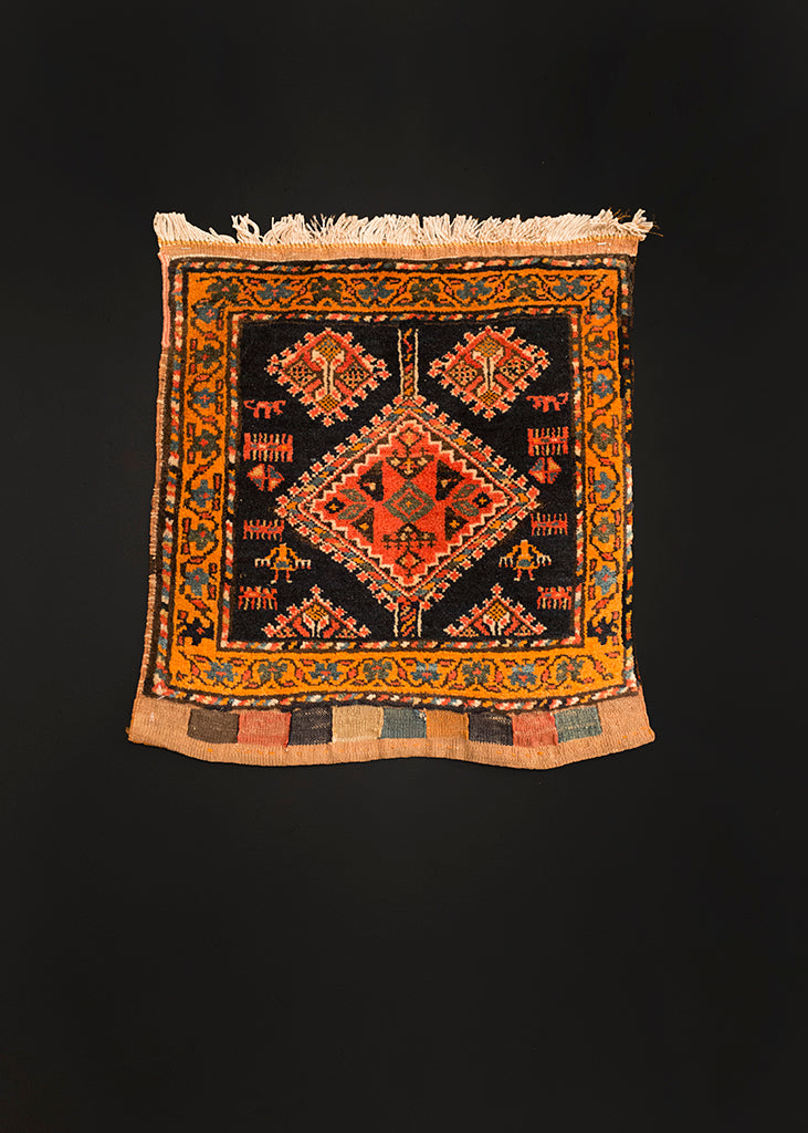 Bag face handwoven by the Qashqa'i circa 1940. Depicts several figures inducing combs and two women around a diamond medallion. Oranges and reds on a dark field.