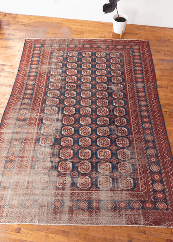 vintage bokhara rug with classic gul pattern in red and blue color palette with some wear especially in the lower left hand corner but foundation is still intact