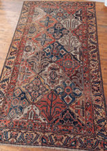 vintage bakhtiari rug with large scale lozenge pattern with garden motifs and serrated leaf and calyx border in earthy reds, yellows, blues, and browns