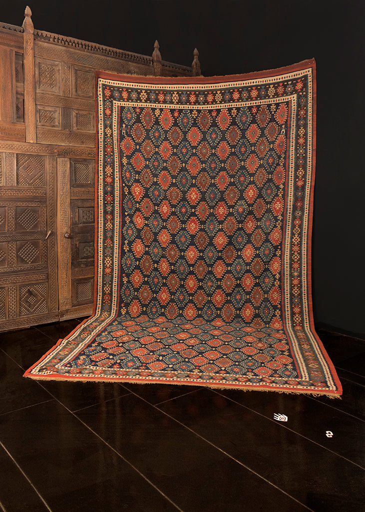 Fine kilim handwoven during early 20th century in Northwest Iran. Small diamond motifs in red and light blue, each outlined in an ivory wavy line. Two hookah smokers in the top corners. Ground is deep blue with borders in ivory and blue.