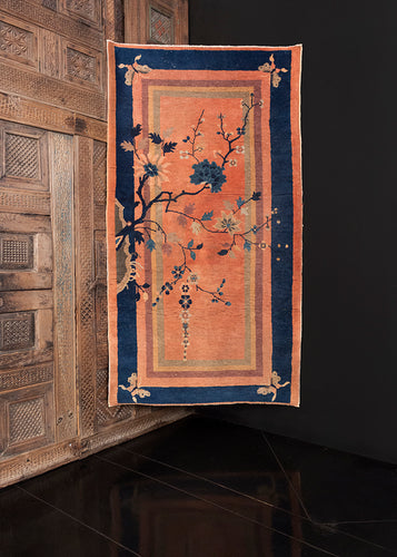 Deco rug handwoven in second quarter of 20th century in Beijing area of China. Peach pink ground with multiple solid borders in indigo, green and yellow. Whimsical with four butterflies, cherry blossom branch growing from one edge.