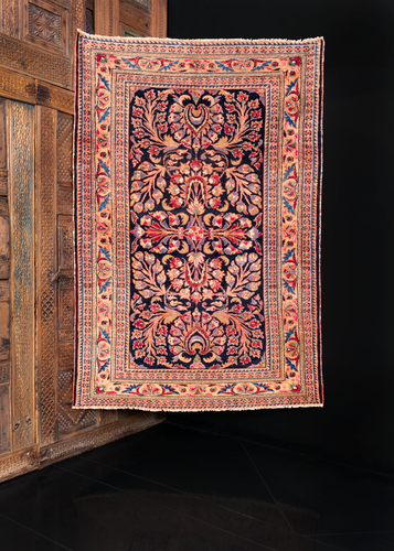 Mehraban rug handwoven during second quarter of 20th century in Western Iran. Detailed floral spray in pink, purple, blue and red atop a black ground.