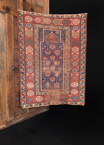 Kazak prayer rug handwoven in the Caucasus during the late 19th century. Bold red and blue color palette with ivory, yellow, turquoise and aubergine as accent colors. Field has a pattern of a lattice containing geometric floral elements topped with a mihrab.