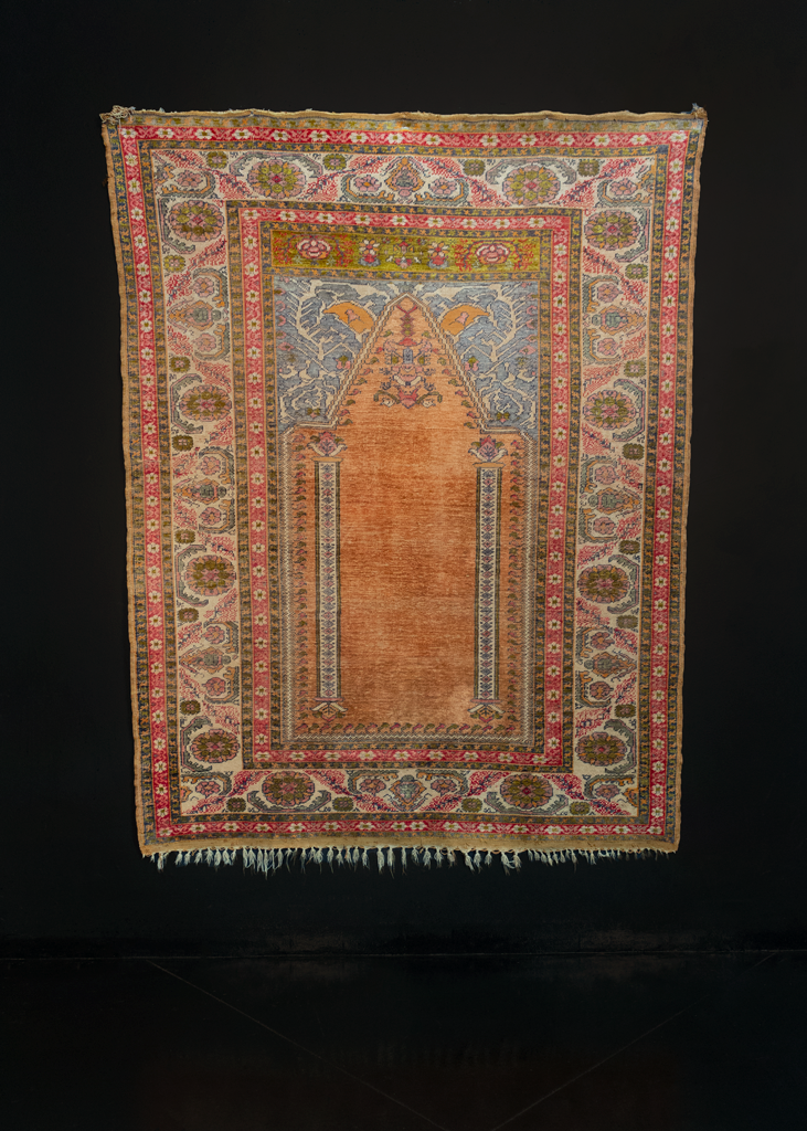 Silk Kayseri handwoven during middle of 20th century in Central Turkey. The Mihrab, or prayer niche, features a velvety orange field with two ivory columns and a hanging lantern. Pink, aqua, chartreuse and siren red.