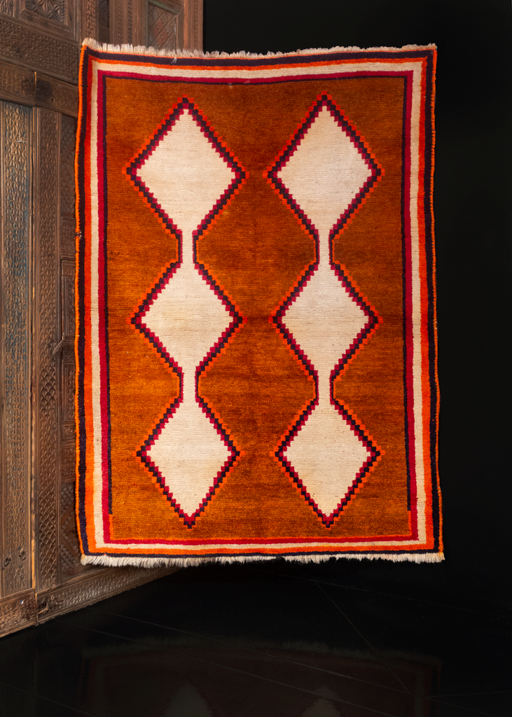 Gabbeh rug handwoven during middle of the 20th century by the Lori of Southern Iran. Simple yet bold filed with two columns of connected diamonds rendered in solid white atop a burnt orange field.