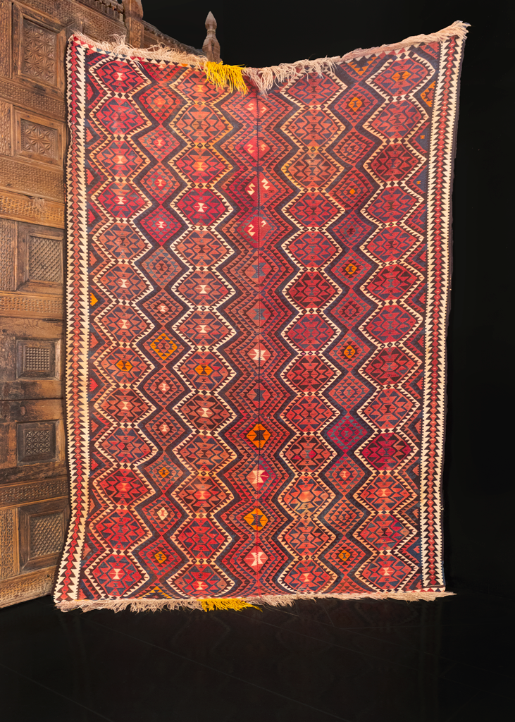 Turkish kilim handwoven during middle of the 20th century. Woven in two panels and stitched down the center. Rows of connected pentagons and diamonds run along the length of the piece. White, orange and yellow atop a red ground.